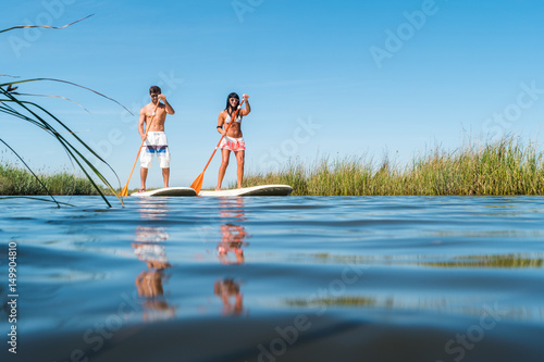 Man and woman stand up paddleboarding