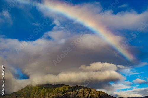 Beautiful hike of green mountains with rainbow shining on volumetric clouds