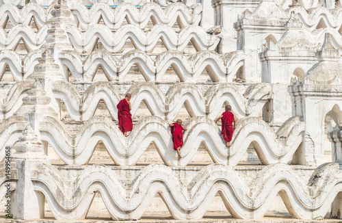 Back side of three young monk are Climbing up on the Mya Thein Tan Pagoda at bag Poster