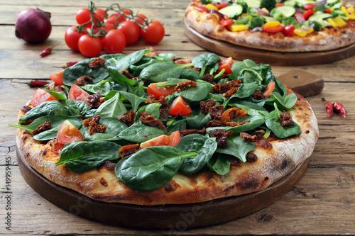 pizza vegetariana con spinaci e pomodori freschi su sfondo rustico