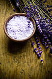 Lavender wellness concept with lavender plants, bowl of salt over old wood background with copy space