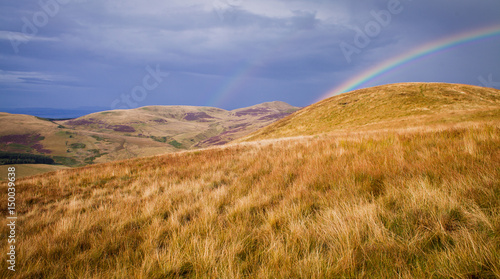 Beautiful Rainbow over Grassy Hills in Scotland.