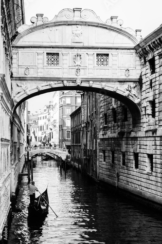 Fototapeta na wymiar Ponte dei sospiri with a gondola floating towards it. Venice, Italy. Black and white.