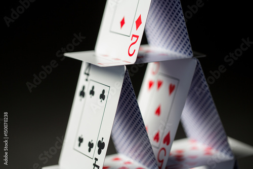 close up of house of playing cards over black плакат