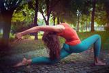 .woman practice yoga in park.woman practice yoga in nature.woman practice yoga in park