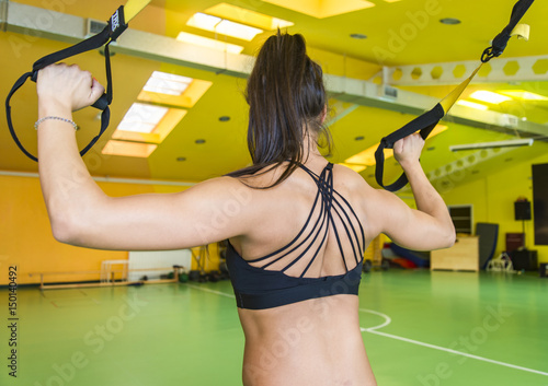 Póster Young woman doing suspension training