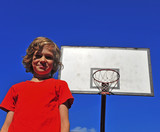 Happy smiling boy with basketball hoop on background