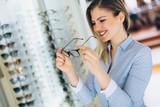 Fototapeta health care, eyesight and vision concept - happy woman choosing glasses at optics store