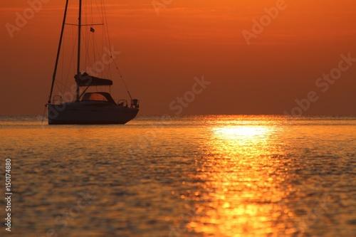 Segelyacht im goldenen Morgenlicht am Meer