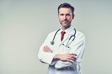 Portrait of handsome doctor standing with crossed arms. Isolated - 150177678