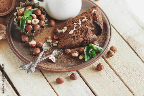 Foto op Canvas Chocolade Piece of chocolate cake, mint leaves, hazelnuts and jar with milk