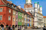 Unidentified people walk past the colourful Craftsmen Houses and Town Hall in Stary Rynek Square, Poznan, Poland