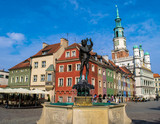 Unidentified people walk past colourful traditional buildings and the Town Hall of Stary Rynek Square in Poznan, Poland