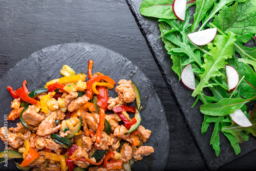 Poster Fry meat with vegetables near salad with arugula and radish on stone slate plates