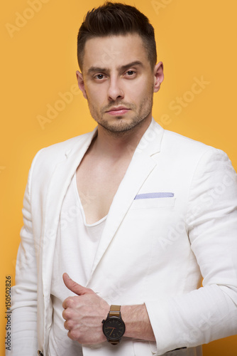 Handsome elegant man in white jacket standing on yellow background Poster