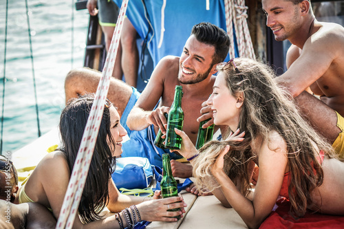 Happy friends toasting beers and chilling beers in boat vacation trip