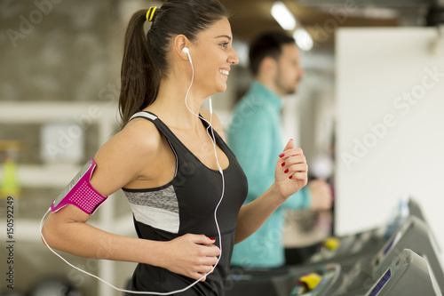 Juliste Young woman running on the treadmill and listening to music at the gym