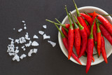 Red hot chili peppers on a green plate with salt crystals nearby on a black background. Asian species.