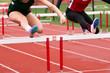 Tow high school Girls racing the hurdles