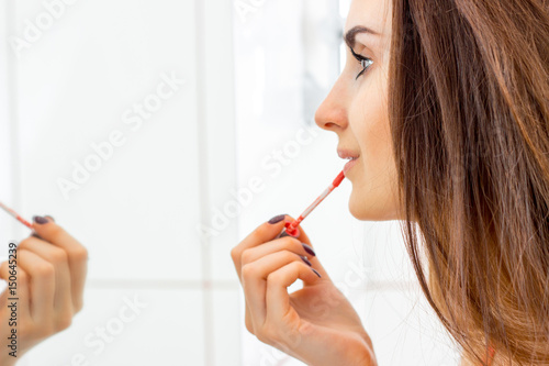 a young girl looks in the mirror and paint lips Poster