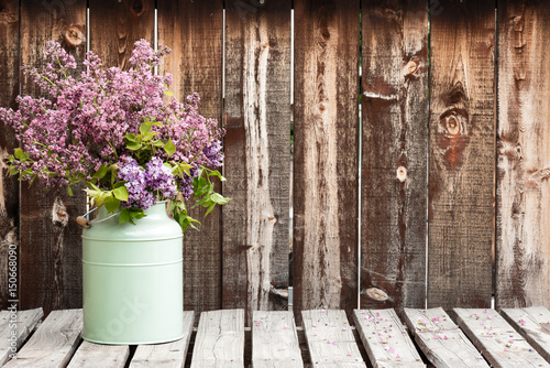 Large bouquet of lilacs in a green container on a rustic wooden table.
