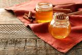 Cinnamon and honey in jars on table