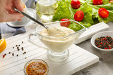 Female hand holding spoon with delicious mayonnaise in gravy boat on kitchen table