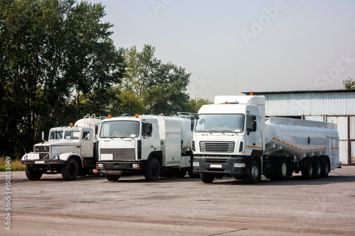 Three white tank truck aircraft refuelers in the parking lot near the garages