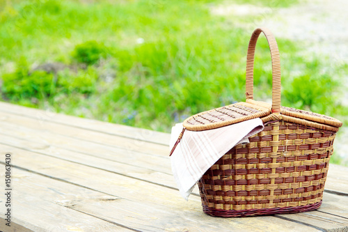 Picnic in nature in the forest. The concept of recreation. Wooden table and wicker basket