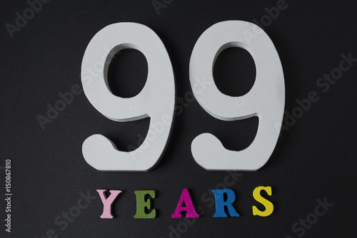 Letters and numbers ninety-nine years on a black background. Poster