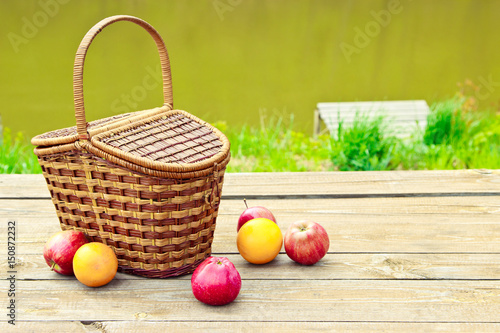 Foto op Canvas Pistache Picnic on the nature in the forest near the river. Wooden table and fruit basket