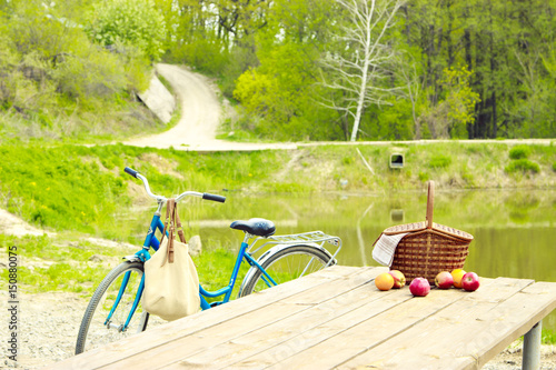 Foto op Canvas Lime groen Picnic in nature in the forest. Wooden table and basket. Traveling by bike
