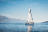 Sailing yacht in the sea against the backdrop of mountains - 150889288