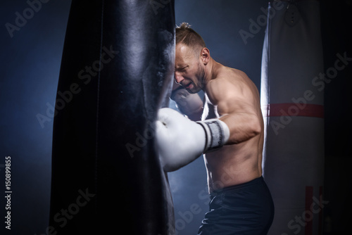 Póster Male boxer using punch bag during training .