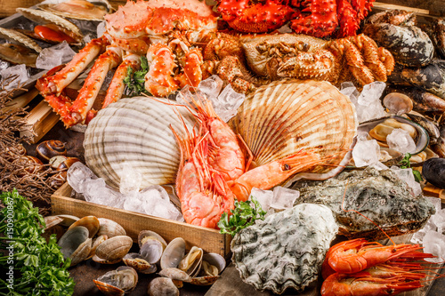 Fototapeta Seafood cuisine plate as an ocean gourmet dinner background. Crab, seashells, oysters, shrimp and other seafood delicacies.