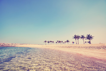 Color toned beautiful beach with crystal clear water, summer holidays concept.