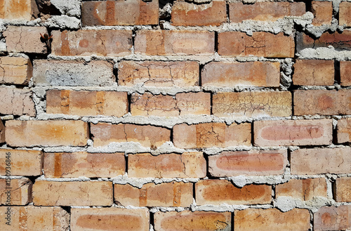 Foto op Plexiglas Baksteen muur Badly laid brick wall with cracks and gaps