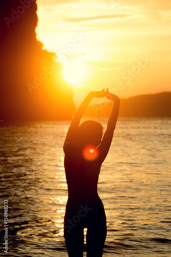 Female body silhouette against bright sea sunset and sunny islands on horizon li Poster