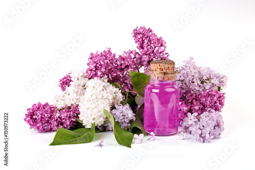 Foto op Canvas Azalea Glass bottle of lilac oil and the blooming branches of lilac on a white background.