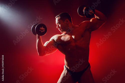 Silhouette of an athletic man. Athlete on a red background.  In the hands of dumbbells.