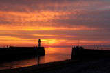 Picturesque deep orange sunset and lighthouse in Normandy, France
