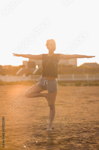 Young girl practices yoga on the beach in the morning at the dawn of the sun Poster
