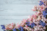 Pink tulips and blue hyacinths on a wooden background