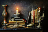 Classic still life with vintage books placed with illuminated candles,pocket watch,pipe,glasses and old copper vase on marble background  - 151093487