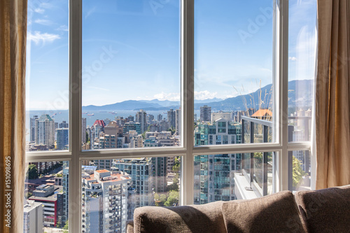 Fotobehang Canada Vancouver, Canada. Penthouse window views of downtown Vancouver skyscrapers, bay and mountains on a sunny day with blue sky. Linen drapes and sofa cushions seen inside.