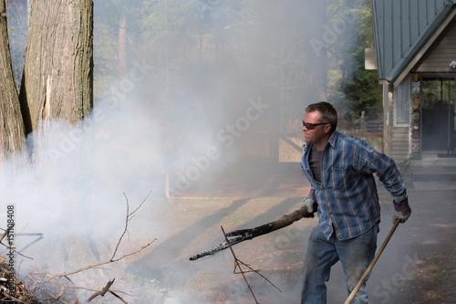 Poster Man doing spring yard work around burn pile.