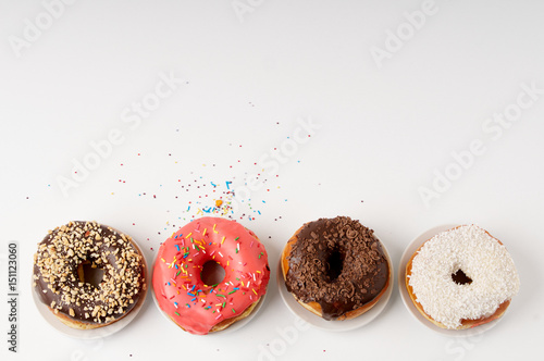 donuts on a plate on a white background Poster