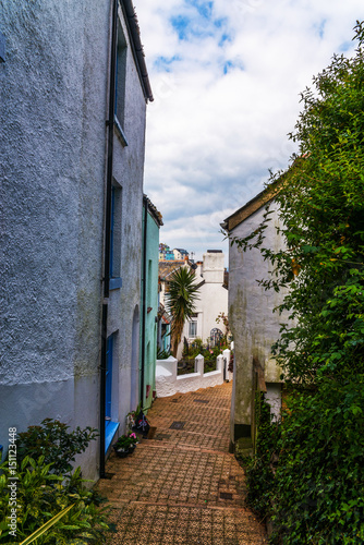 Narrow passage from the back of buildings in seaside town, old architecture, stone walls, historic buildings