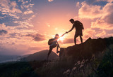 Fototapety Team work, life goals and self improvement  concept. Man helping his female climbing partner up a steep edge of a mountain.