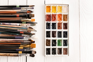 Set of watercolor paints and paintbrushes for painting on wooden table